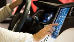 A person sitting in a car and operating the navigation system via the touch display.