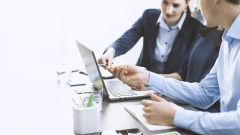 This image shows a business team working together at a desk.