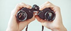 This image shows male hands holding binoculars.